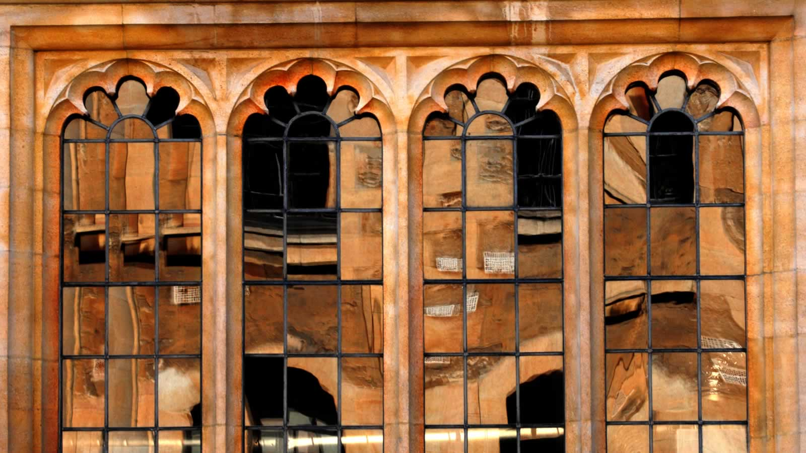 The windows of the Divinity School reflecting the Sheldonian Theatre in the sunshine